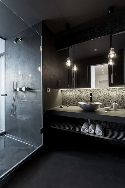 black modern bathroom with a concrete countertop and a tiled shower