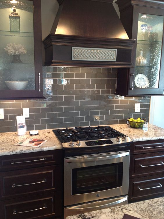 35 ways to use subway tiles in the kitchen digsdigs for Brown kitchen cabinets with black appliances