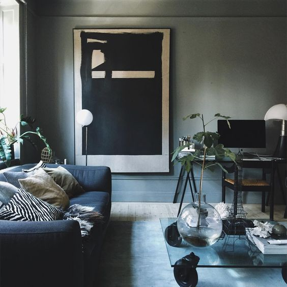 grey walls, a navy sofa and a modern large scale artwork