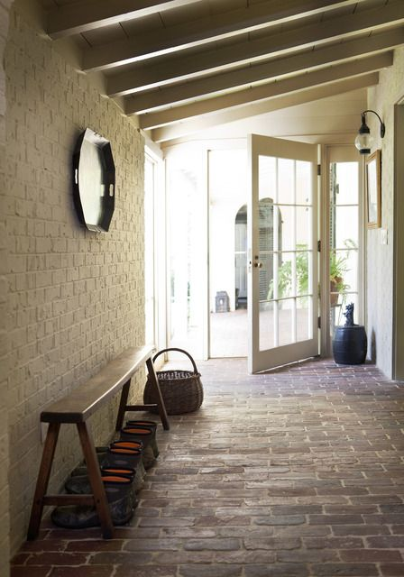 neutral brick walls and red brick floors for a rustic entryway