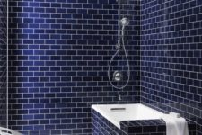 25 navy blue subway tiles on the walls and bathtub