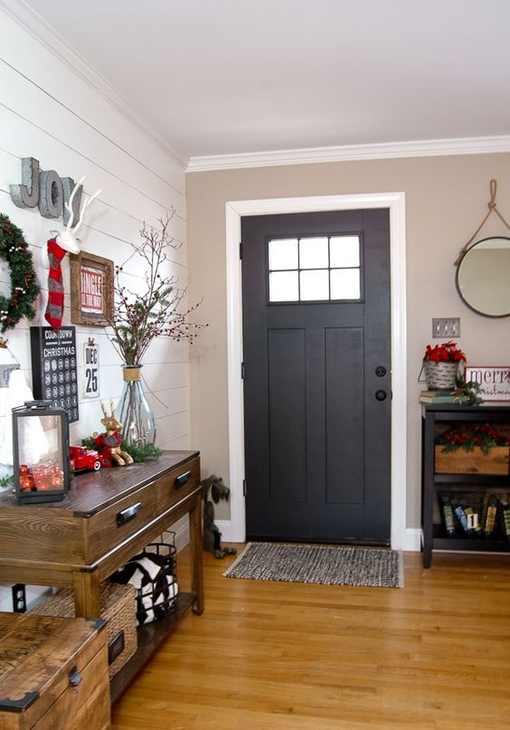 a faux deer head, a lantern filled with ornaments and an evergreen wreath