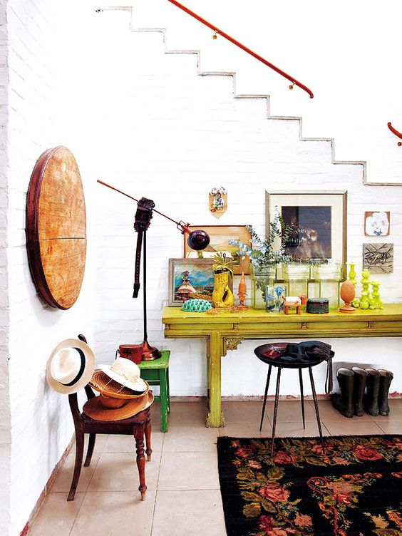 eclectic mudroom with white brick walls and bold furniture