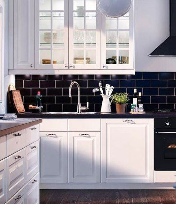 navy subway tiles and black countertops make white cabinetry stand out