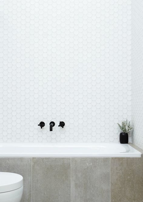 white large penny tiles over the bathtub