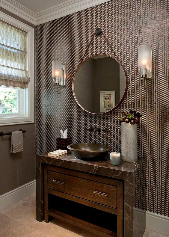 penny tiles in the shades of brown highlights the sink and a marble counter