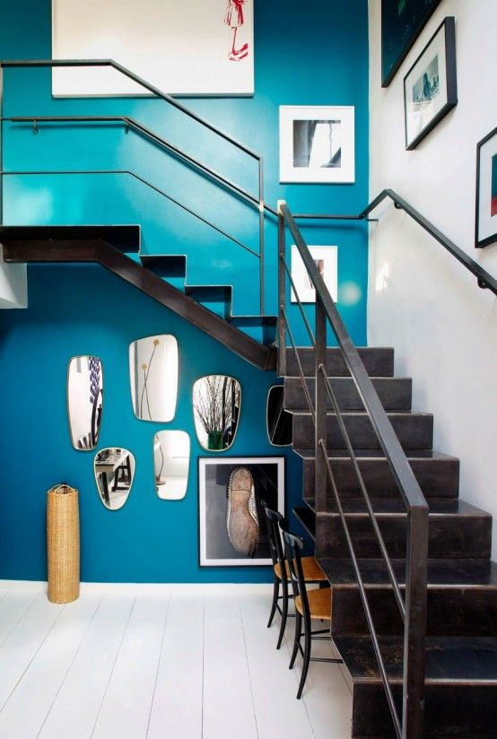 bold blue wall with artworks to make the space chic