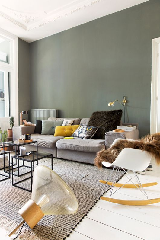 calm room in the shades of grey with a green wall and accents