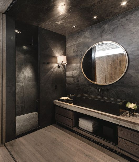 moody bathroom with a huge sink, wooden floor and cabinets
