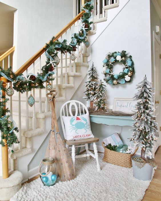 coastal Christmas entryway decor in pale blue, with a garland, a wreath, some trees and ornaments