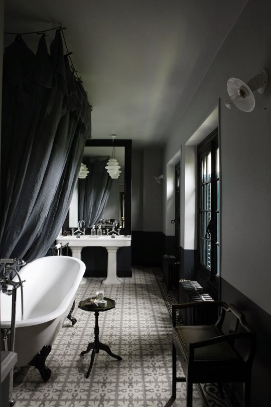 moody vintage bathroom with white sinks and a bathtub, vintage furniture makes up the space
