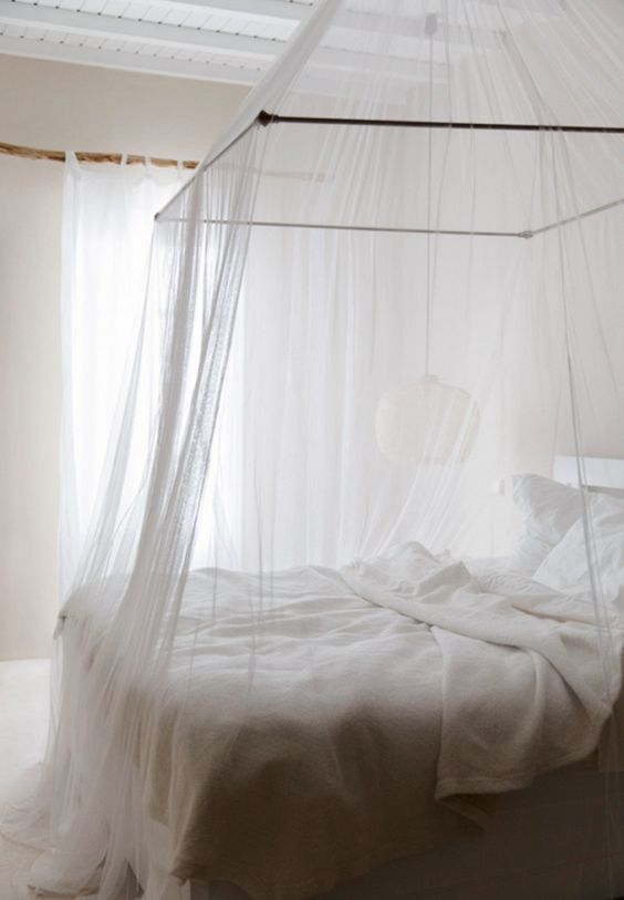 canopy bed with very thin transparent fabric to make the bed look inviting