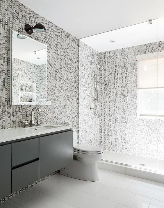 gray kids' bathroom features grey hex tiles on the wall and they continue to the shower