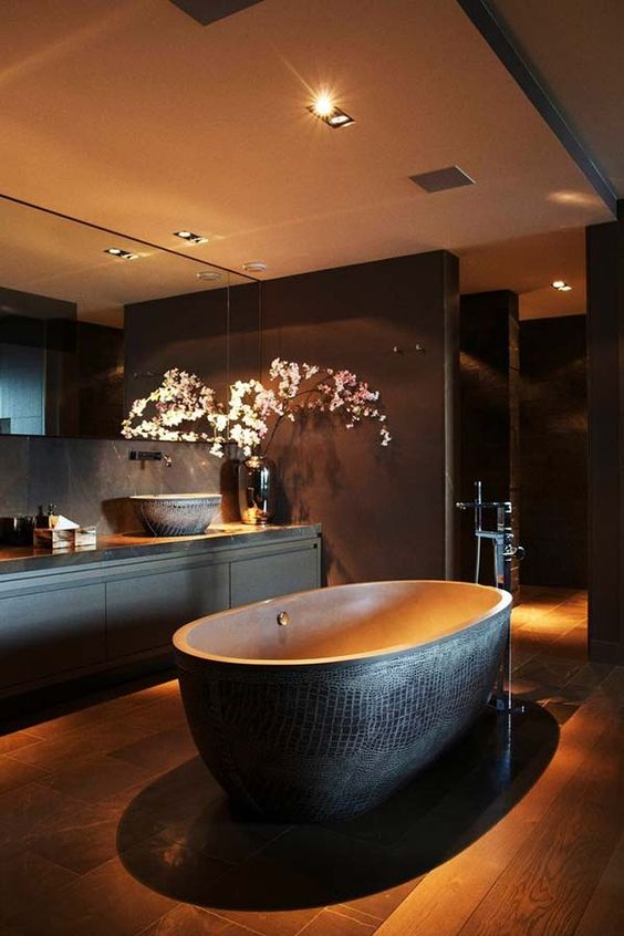 spacious dark bathroom, a free-standing bathtub with a textural look