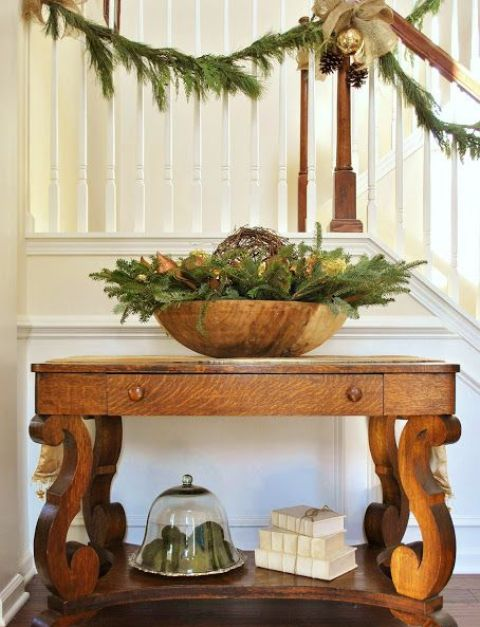 large wooden bowl with fir branches and lights is enough to set up a mood