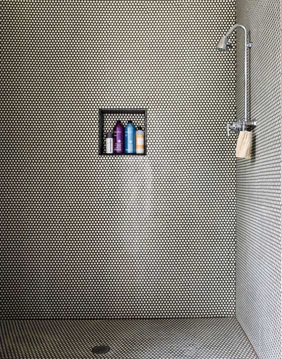 white penny tiles with black grout adds texture to the shower space