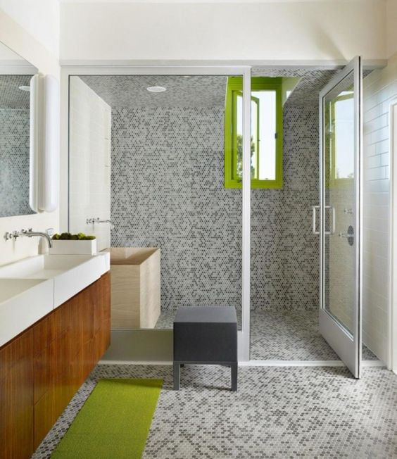 grey tiles on the walls, floor and in the shower contrast with lime green  accents
