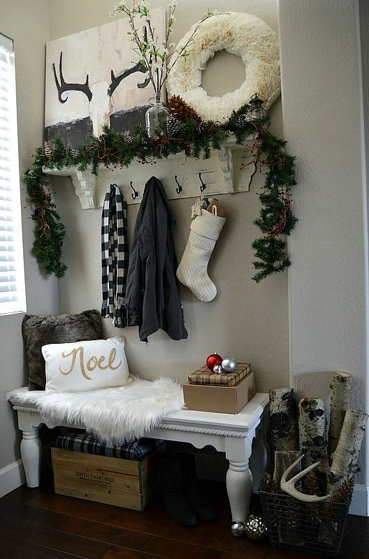 white tissue paper wreath, a fir garland, a couple of ornaments and logs give this entryway a wintry look