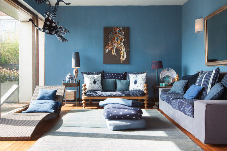 This living area is painted in blue and features lots of blue pillows in different shades. They looks great highlighted by natural wood in brown shades. (Domus Nova)
