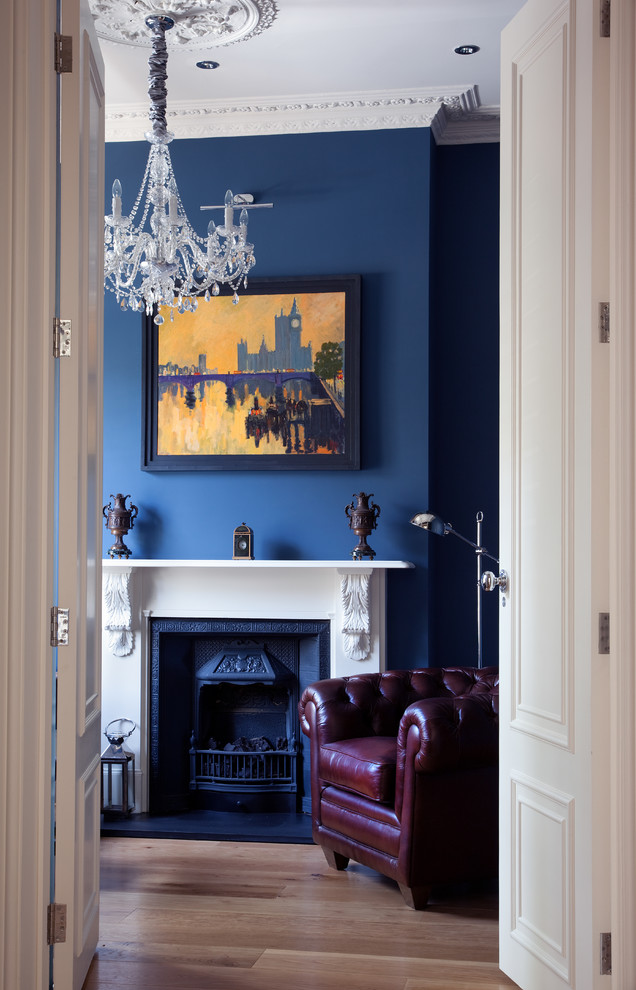 A brown leather armchair with a glamour crystal chandelier looks greet against deep blue wall. (Paul Craig Photography)