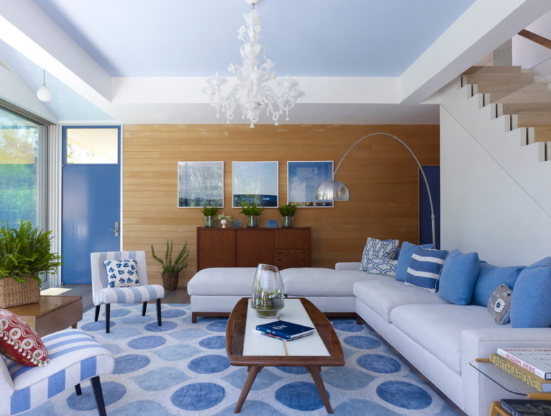 This contemporary coastal-inspired room features amazing dark brown wood furniture and lots of blue accents in different shades and patters. (Austin Patterson Disston Architects)
