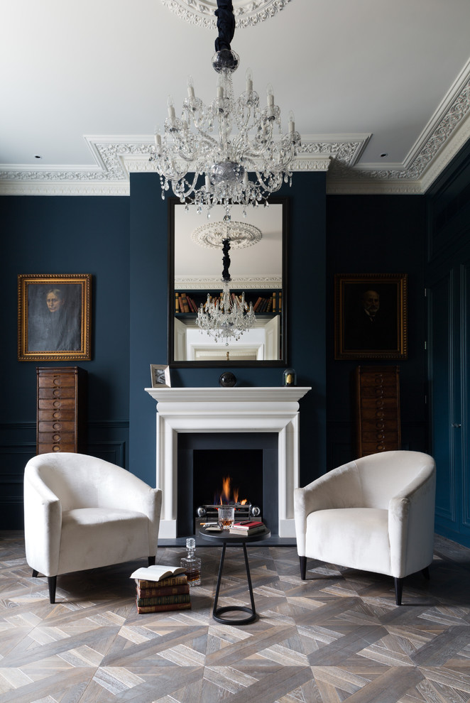 Walls of this his glamour living area are painted in really dark blue color but lots of white makes it not that moody. Vintage wood cabinets looks like their are supporting gorgeous portraits hanging on these walls. (Cochrane Design)