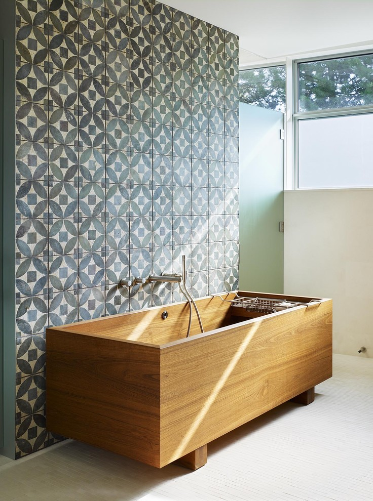 a striking full-size wooden bathtub looks great against a geometric accent wall (Abramson Teiger Architects)