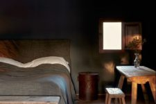 rustic bedroom decor with dark walls, upholstered bed and rough wooden furniture
