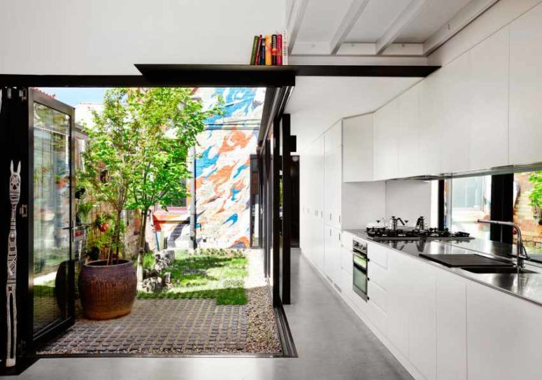 The kitchen is done in white, it's modern and functional and the space is extended outdoors to the sunlit backyard