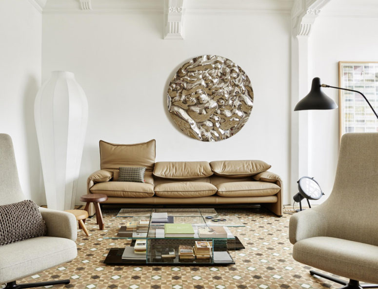 The living room is a spacious and airy room that incorporated comfy ivory and beige furnishings and mosaic tile floors