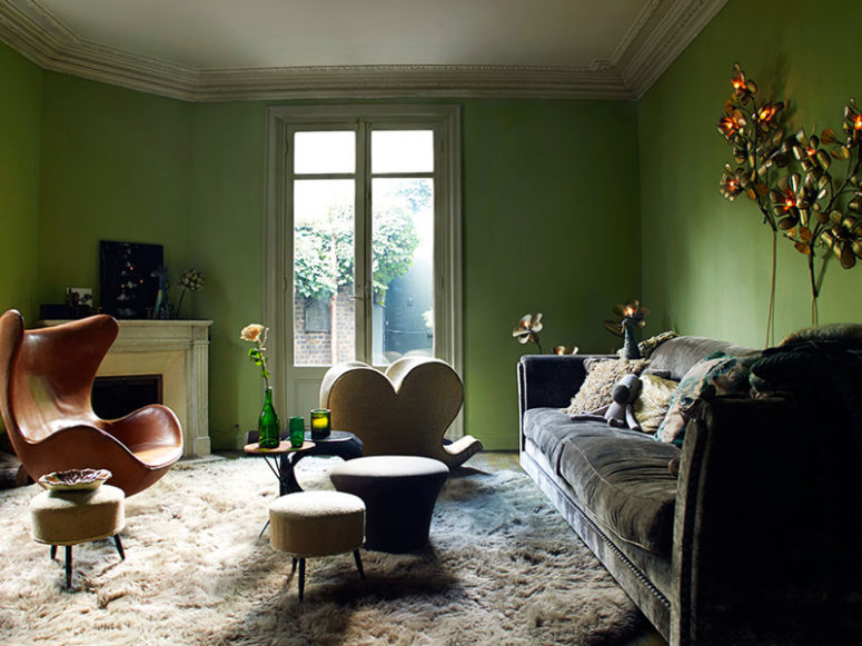 The living room is done in green, there are flower and leaf-shaped lamps, faux fur and velvet, bold chairs