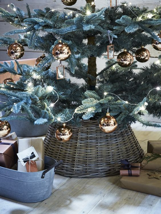 a christmas tree with copper ornaments and a basket that hides the tree base
