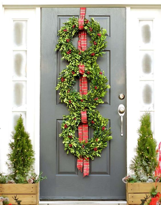 a boxwood wreath tirio on the door small evergreen trees with lights