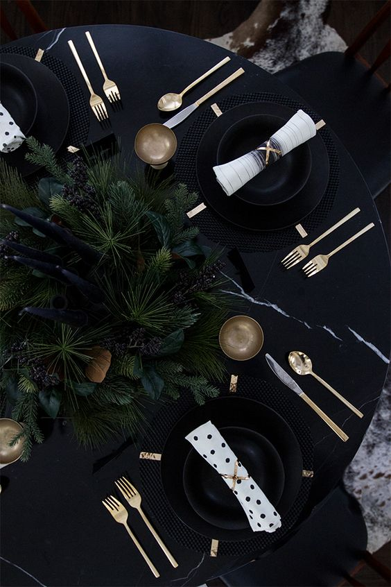 black tablescape with moody evergreens and black candles
