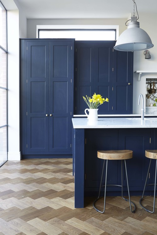 Ligt-colored parquet contrasts with navy cabinets and the kitchen is flooded with light through the window wall