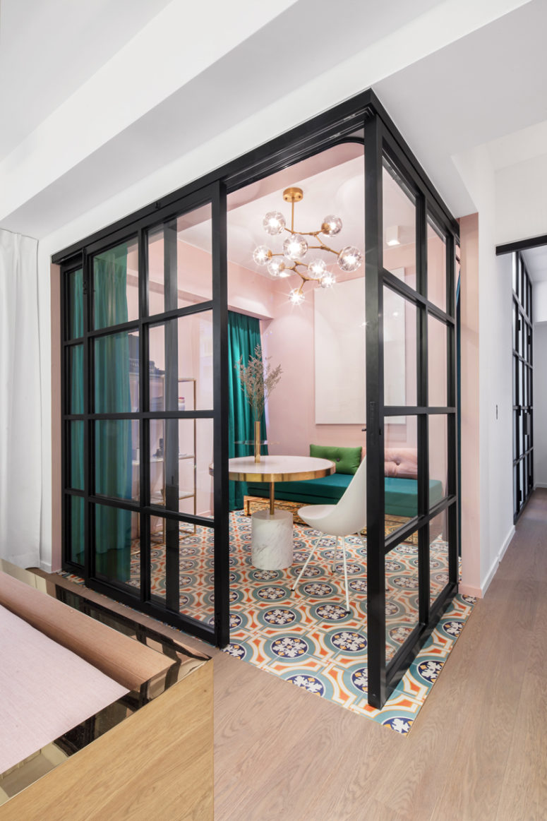Suspended metal, double-sliding glass doors and dark jade drapery fully transform the level of privacy in the space