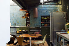 03 The moody kitchen is done with an industrial vibe, the blue and green tiles rule the space