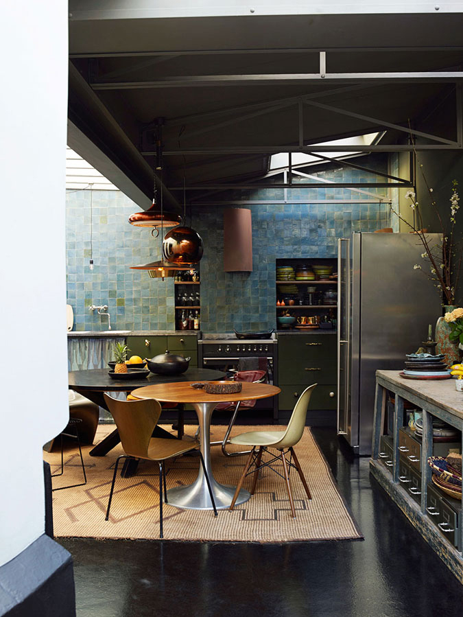 The moody kitchen is done with an industrial vibe, the blue and green tiles rule the space