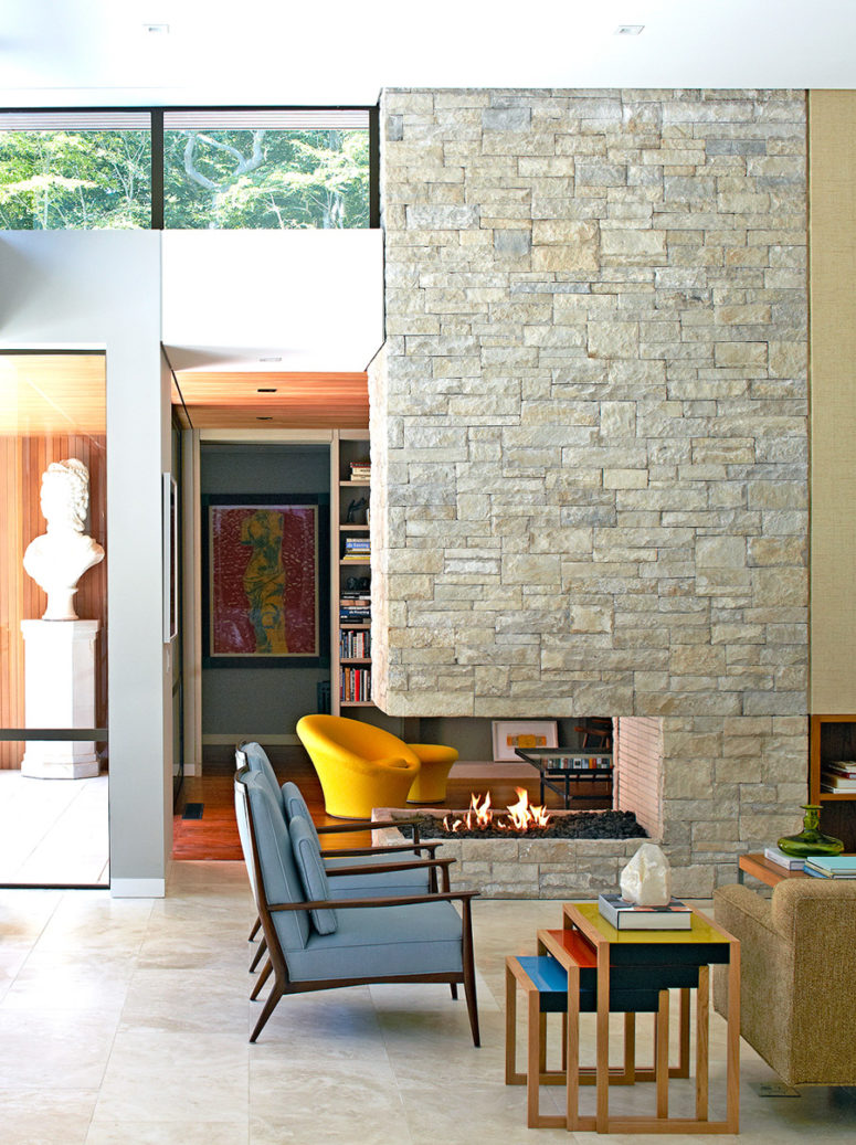 The stone-clad fireplace wall divides the living room into two parts