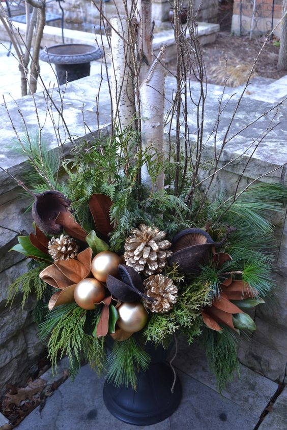 a chic brown and gold Christmas urn with leaves, ornaments and gilded pinecones