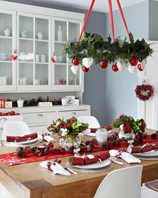 a red and white Christmas chandelier, a red table runner and berries for decor