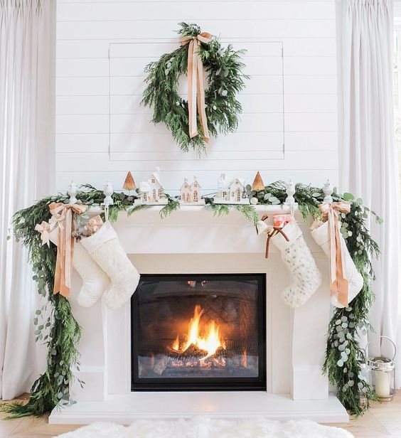 evergreen garland and wreath, bows and small houses make the fireplace very cozy