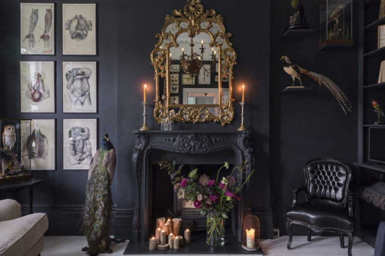 the antique fireplace is a focal point with candles and a refined gilded frame mirror