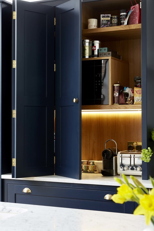 The cabinets hold the appliances and are lit up inside for comfort