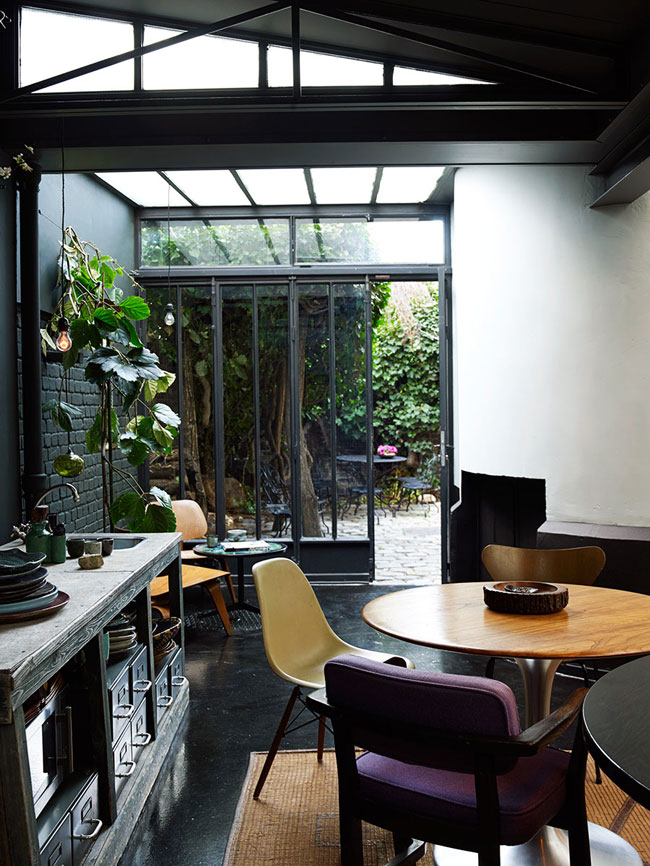 The glazed wall and ceiling fill the house with light, which is essential for a moody kitchen