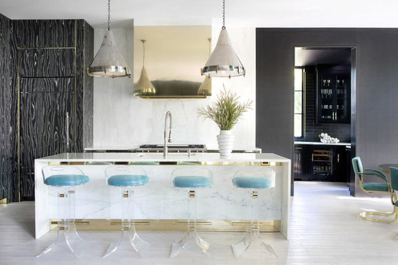 The kitchen island doubles as a breakfast zone and cheers up with gold touches and lucite chairs