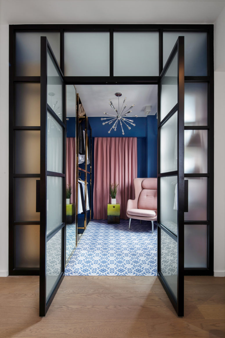 The retail-inspired walk-in wardrobe is complete with custom freestanding polished brass closets