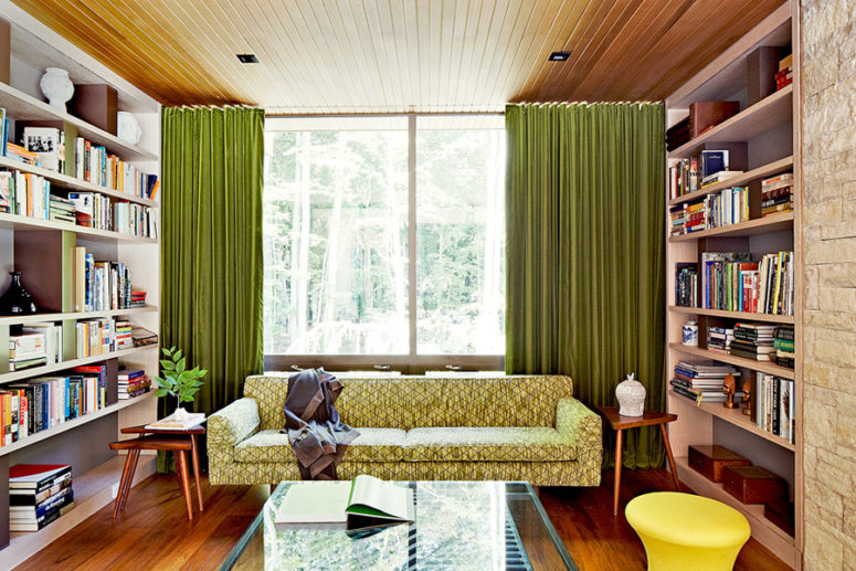 The second living room part is a small and cozy library decorated in bold and cheerful colors