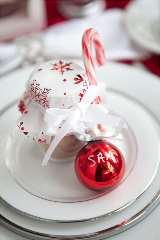 a red ornament as a place card, a cocoa jar with red and white cloth