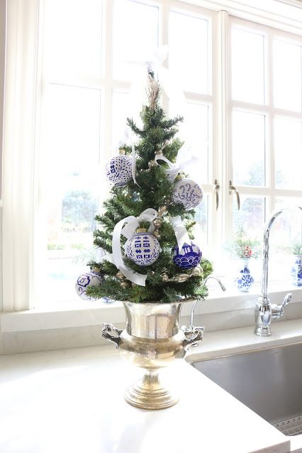 a tabletop tree placed in a gold urn with blue and white ornaments